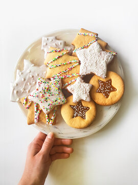 Hand holds a plate with a Christmas cookie on a white background