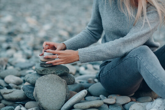 Young woman builds stone stacks pyramid on pebble beach