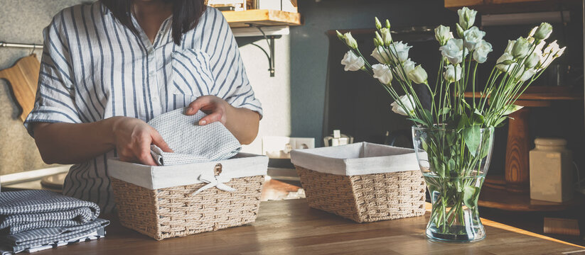 Girl spring cleaning in the kitchen. Piles kitchen towels in baskets. Spring cleaning, decluttering, cleaning space, cleaning agency