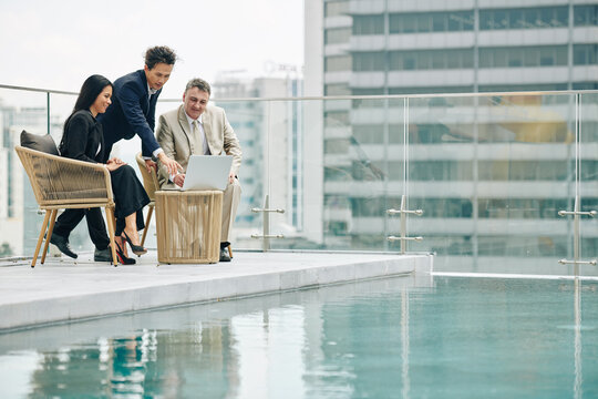 Group of successful business people meeting on rooftop by swimming pool and discussing presentation on laptop screen