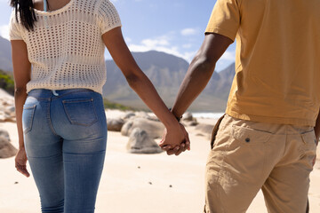 Midsection of african american couple walking holding hands on a beach by the sea