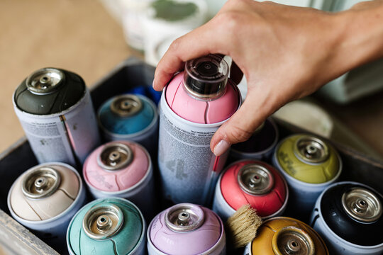High angle of unrecognizable crop female artist taking spray paint from box in art studio