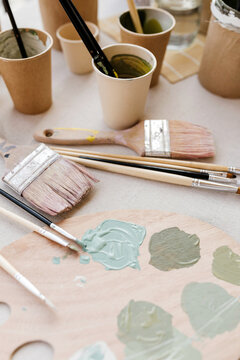 Top view of wooden palette with pastel green paints and professional brushes on table in workshop