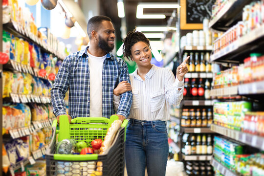 Cheerful Black Spouses Choosing Food In Grocery Store