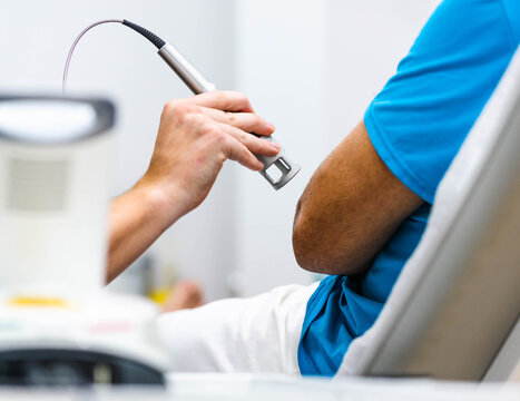 Unrecognizable cropped doctor using laser probe to heal elbow of crop patient during physiotherapy session in modern clinic