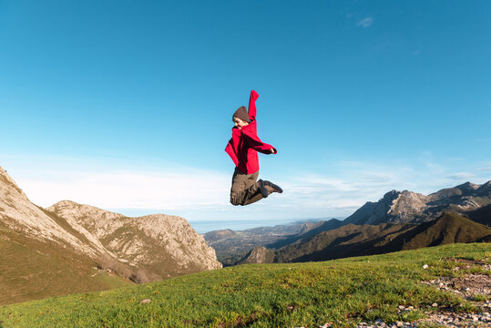 Side view of excited hiker jumping above ground in highlands and enjoying summer vacation in El Mazuco