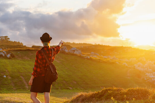 Back view of anonymous explorer in checkered shirt standing on hill and pointing away at sunset sky during summer travel