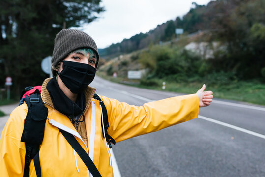 Female backpacker in yellow raincoat and protective mask standing with thumb up on roadside while hitchhiking in Asturias in autumn