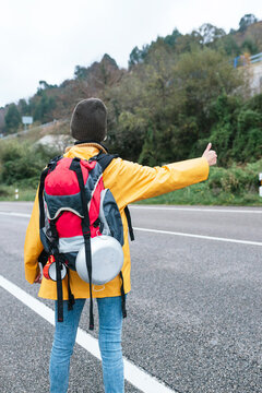 Back view of female backpacker in yellow raincoat standing with thumb up on roadside while hitchhiking in Asturias in autumn