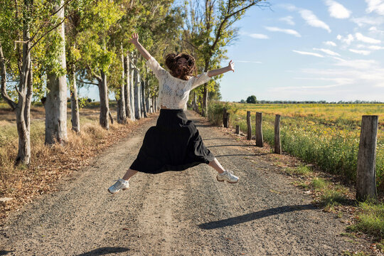 Delighted female jumping with outstretched arms and enjoying sunny weather in countryside in summer