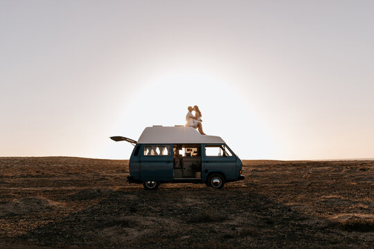 Side view of loving couple of travelers sitting on roof of van and tenderly kissing on background of sundown in savanna