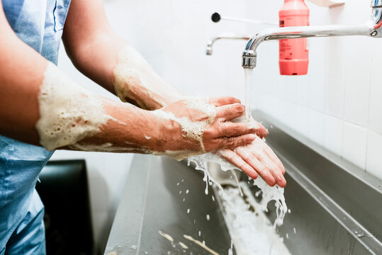 Side view of crop unrecognizable surgeon washing hands with soap over sink while preparing for medical procedure in hospital