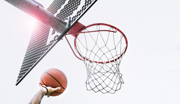 From below of crop hand of anonymous male player shooting ball to hoop while playing basketball on sports ground on street