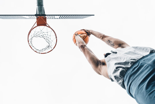 From below of unrecognizable sporty male throwing basketball ball into hoop while playing game on street sports ground