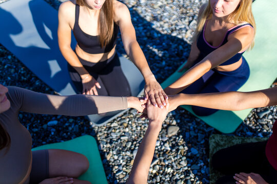 unity group of women practic yoga on rhe beach in morning