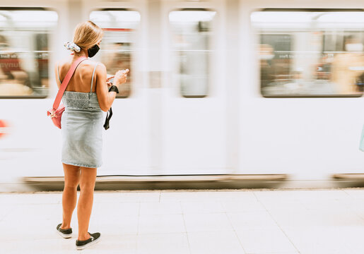 Back view of unrecognizable young female passenger in casual outfit and black protective mask standing on platform of subway station and checking information on mobile phone