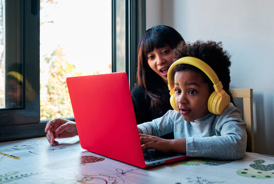 Cheerful black mother sitting at table with curious boy in headphones and playing together interesting video game on laptop at home