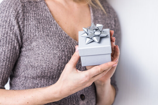 Unrecognizable crop female standing with Christmas present in gift box on white background in studio