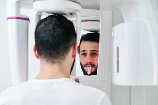 Calm male patient using modern 3d dental scanner in bright clinic during appointment