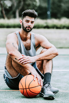 Full body of serious muscular young bearded basketball player in sportswear sitting near ball on street playground and looking at camera