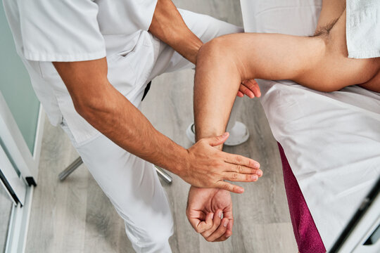 From above of unrecognizable crop male osteopath massaging arm of patient during therapeutic session in clinic