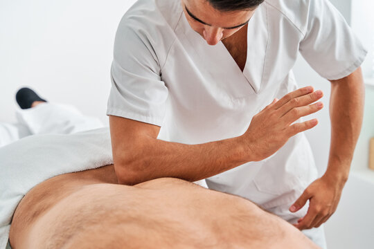 Serious male osteopath doing massage on back of unrecognizable patient in bright medical room of modern clinic during physiotherapy treatment