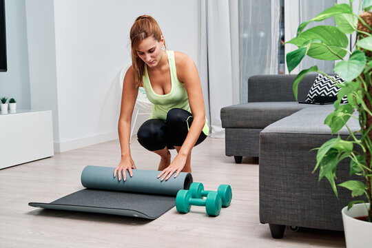 Calm female in activewear standing on floor and twisting mat after training at home