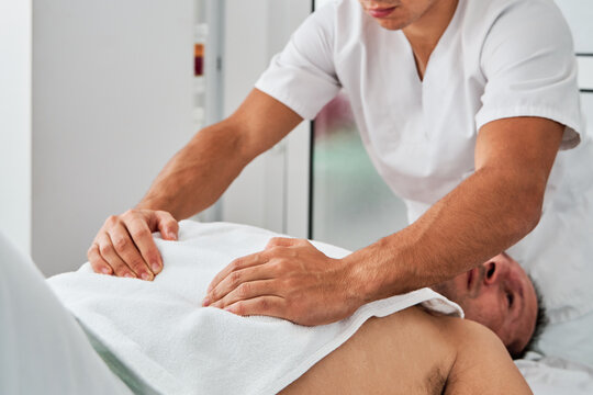 Male patient getting massage of stomach during osteopathy session in modern clinic