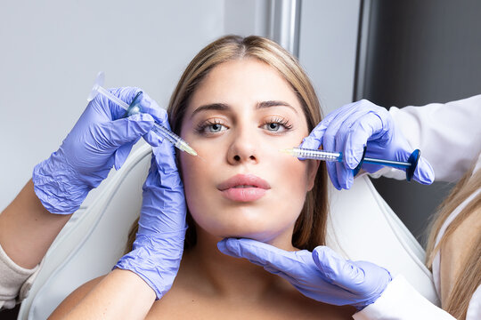 Graceful young female client with long blond hair sitting on medical chair while cut unrecognizable cosmetologists in latex gloves making rejuvenating facial injections procedure in beauty center