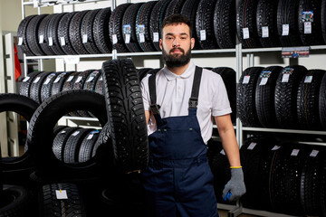 mechanic holding a tire and showing wheel tires at car repair service and auto store shop, young bearded male in uniform working in automobile repair garage