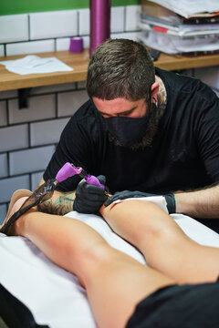 Unrecognizable concentrate bearded male master in black face mask and gloves creating tattoo on arm of crop faceless client in salon