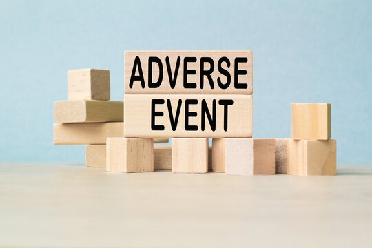 the word ADVERSE EVENT is written on a wooden cubes structure . Cube on a bright background. Can be used for Medical concept. the medicine.