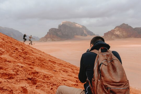 Back view of male traveling photographer taking pictures of people running down sandy hill in Wadi Rum sandstone valley during vacation in Jordan