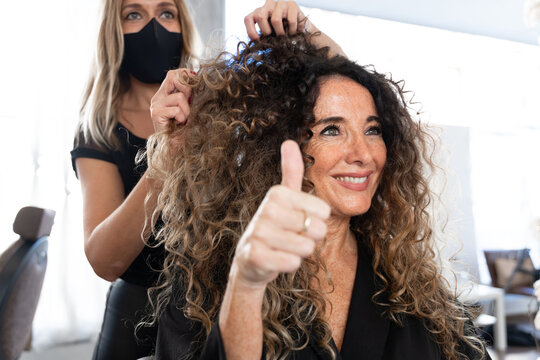 Professional hairdresser in black protective mask using curling tongs while making hairdo to long haired female customer in salon