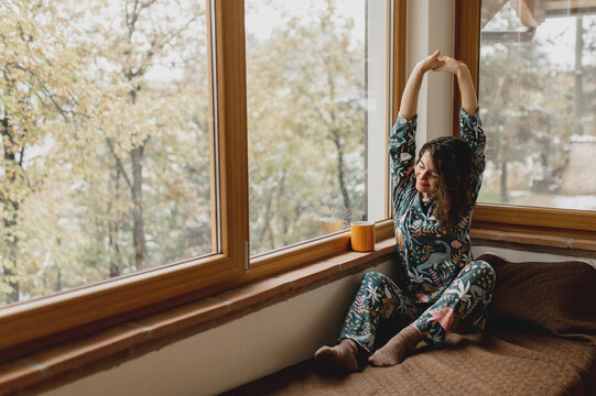 Close up caucasian attractive woman portrait waking up and stretching. Lady sitting on the bed in a beautiful full of glass windows bedroom with cup of tea or coffee. Winter landscape and warm of domestic life.