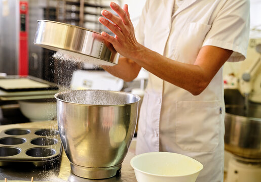 Cropped unrecognizable female chef in white uniform and hat sifting flour into metal bowl while preparing dough for pastry in bakery kitchen