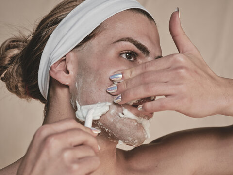 Shirtless androgynous young guy with manicure holding hand on waist and looking away while shaving face