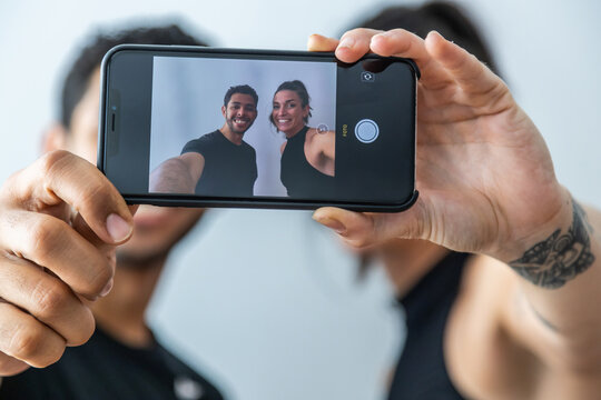 Delighted friends using smartphone and taking self portrait while smiling on white background