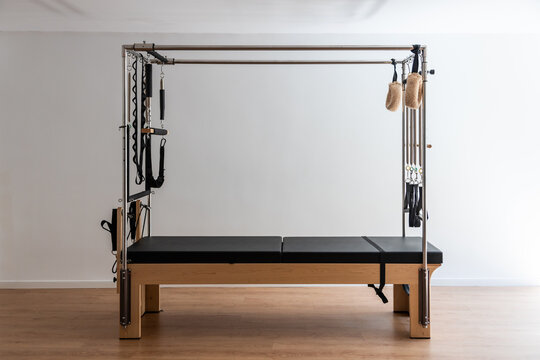 Contemporary pilates cadillac reformer placed on wooden floor in bright sports club at daytime