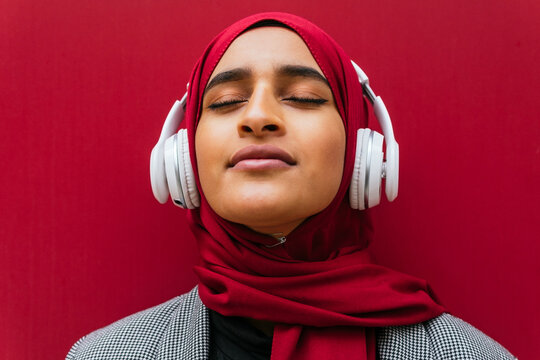 Dreamy Arab female in wireless headphones and traditional hijab standing near urban red building and enjoying music with closed eyes