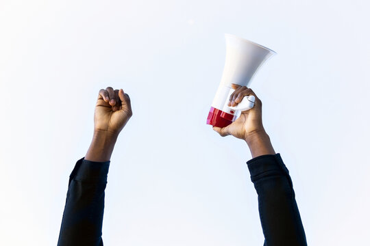 Unrecognizable crop African American male with red and white megaphone standing with fist up on white background