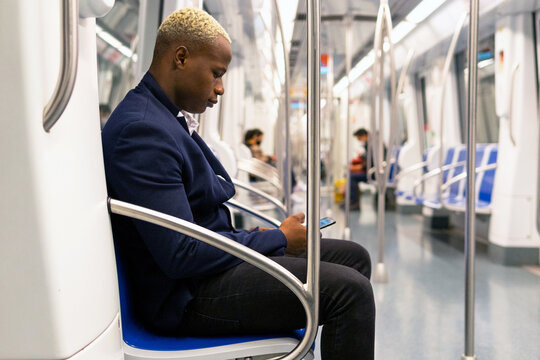 Side view of African American male entrepreneur in suit sitting in modern underground carriage and messaging on cellphone while commuting to work