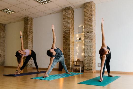 Full body man and women in sportswear doing Trikonasana pose on mats during group yoga lesson in studio