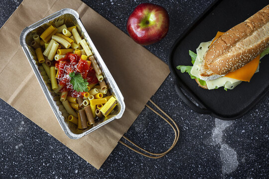 Top view composition with containers with pasta and sandwich placed with fresh red apple on table with paper bag