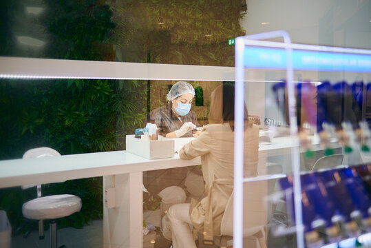 Through glass view of nail artist in mask and gloves sitting at table and doing manicure for customer in beauty salon