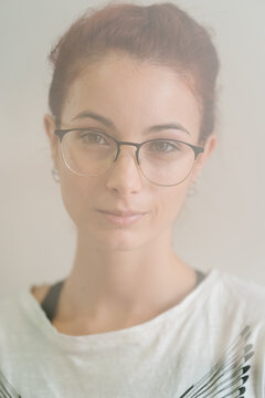 Clever young female in glasses smirking and looking at camera against gray background