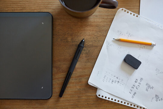 Top view of arrangement of sheet of paper with handwritten notes and modern graphics tablet with stylus on wooden table