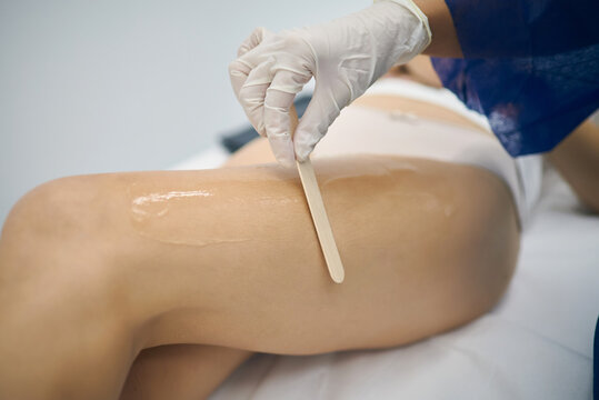Unrecognizable beautician applying sugar paste with wooden spatula on leg of client while removing hair during skin care procedure in beauty clinic