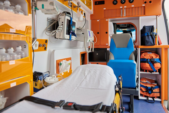 Interior of contemporary ambulance car equipped with various professional instruments and medical stretcher