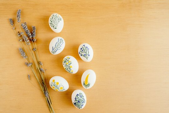 Top view of chicken eggs painted with aquarelle placed on table with lavender flowers and burning candle for Easter